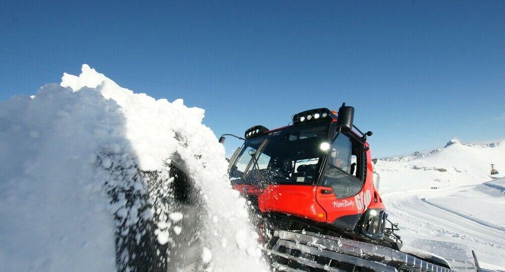 PistenBully 600 Polar schiebt Schnee mit dem Schild.